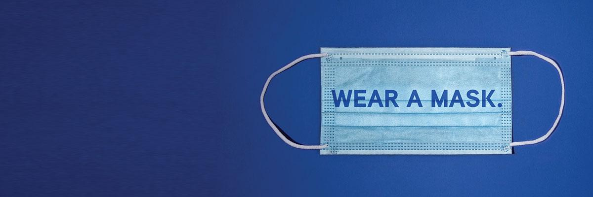 "Wear a Mask For All the Things You Love. A blue surgical mask with the words ""Wear a mas."" overlayed on it."